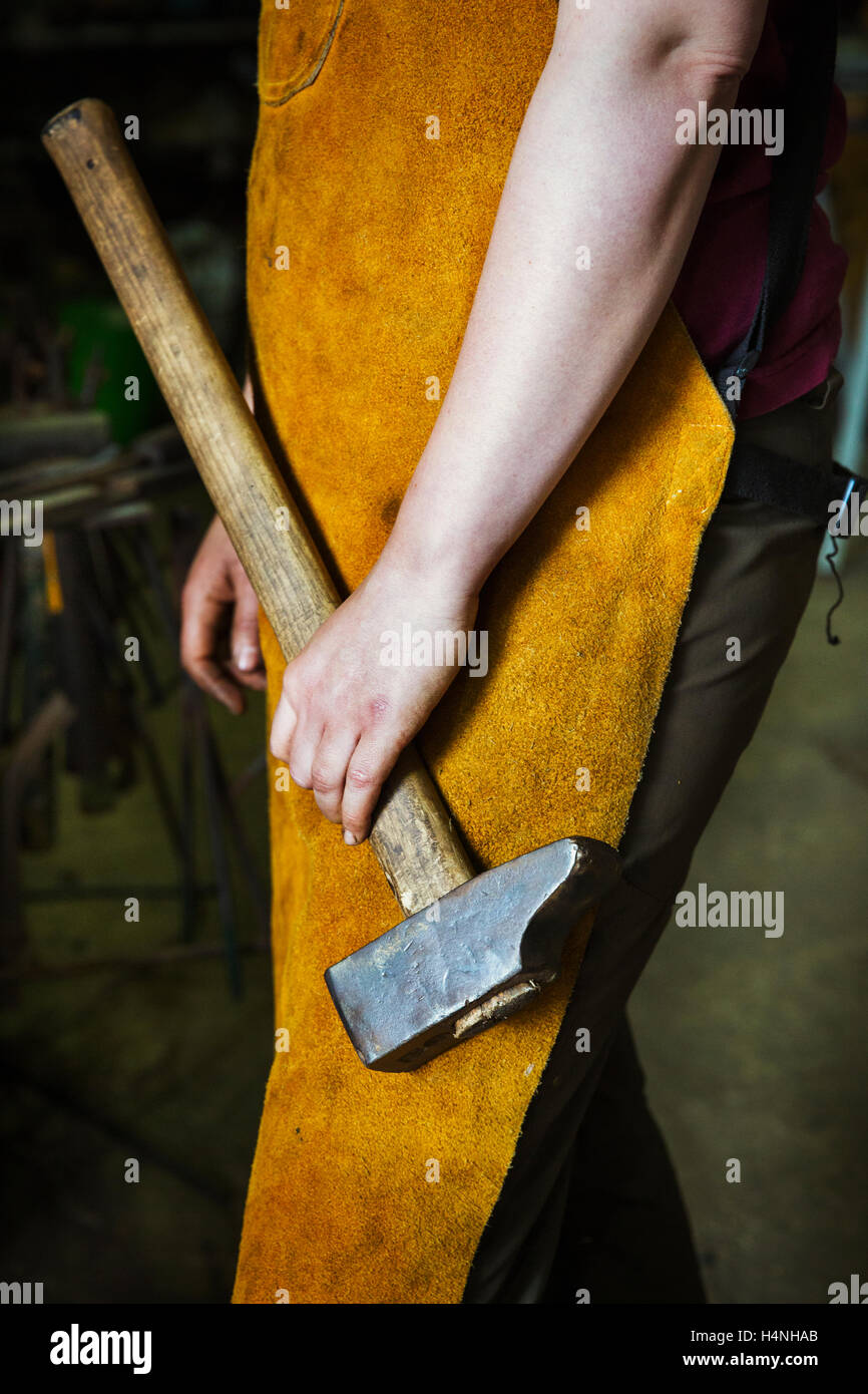 A blacksmith in a heatproof apron holding a large hammer. - Stock Image