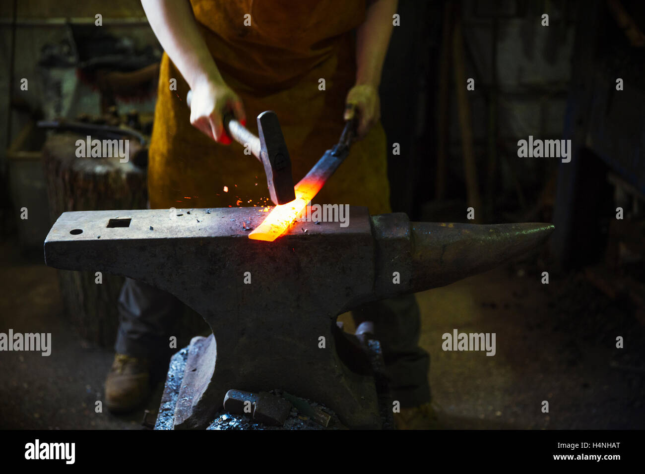 A blacksmith strikes a length of red hot metal on anvil with a hammer in a workshop. Stock Photo