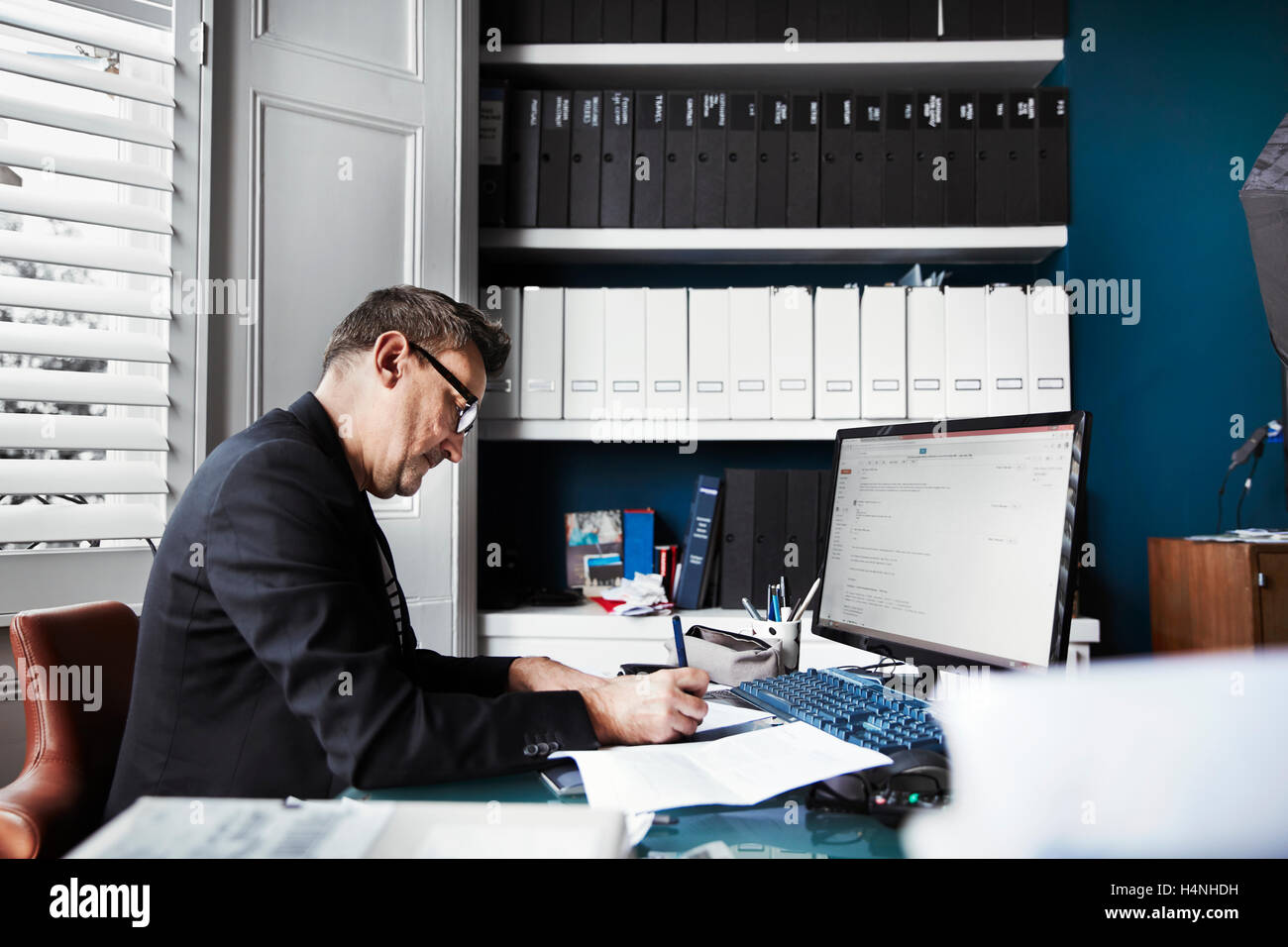 A man sitting at a desk in office, writing on a piece of paper. Neat rows of files on shelves and papers on the - Stock Image