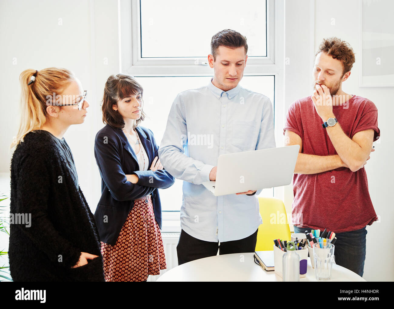 Four people around a table at a business meeting, looking at a laptop screen. - Stock Image