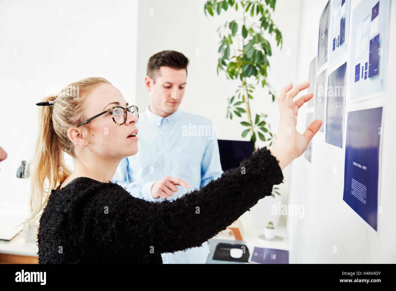 Two people looking at printed plans stuck on a wall, project management and discussions. Stock Photo