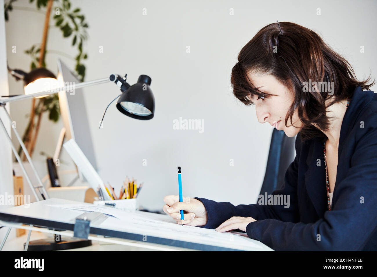 A woman working on a graphic on a drawing board, outlining letters with a pencil. - Stock Image