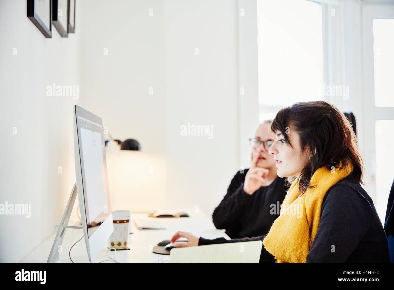 Two women seated sharing a computer screen and discussing the graphic content. - Stock Image