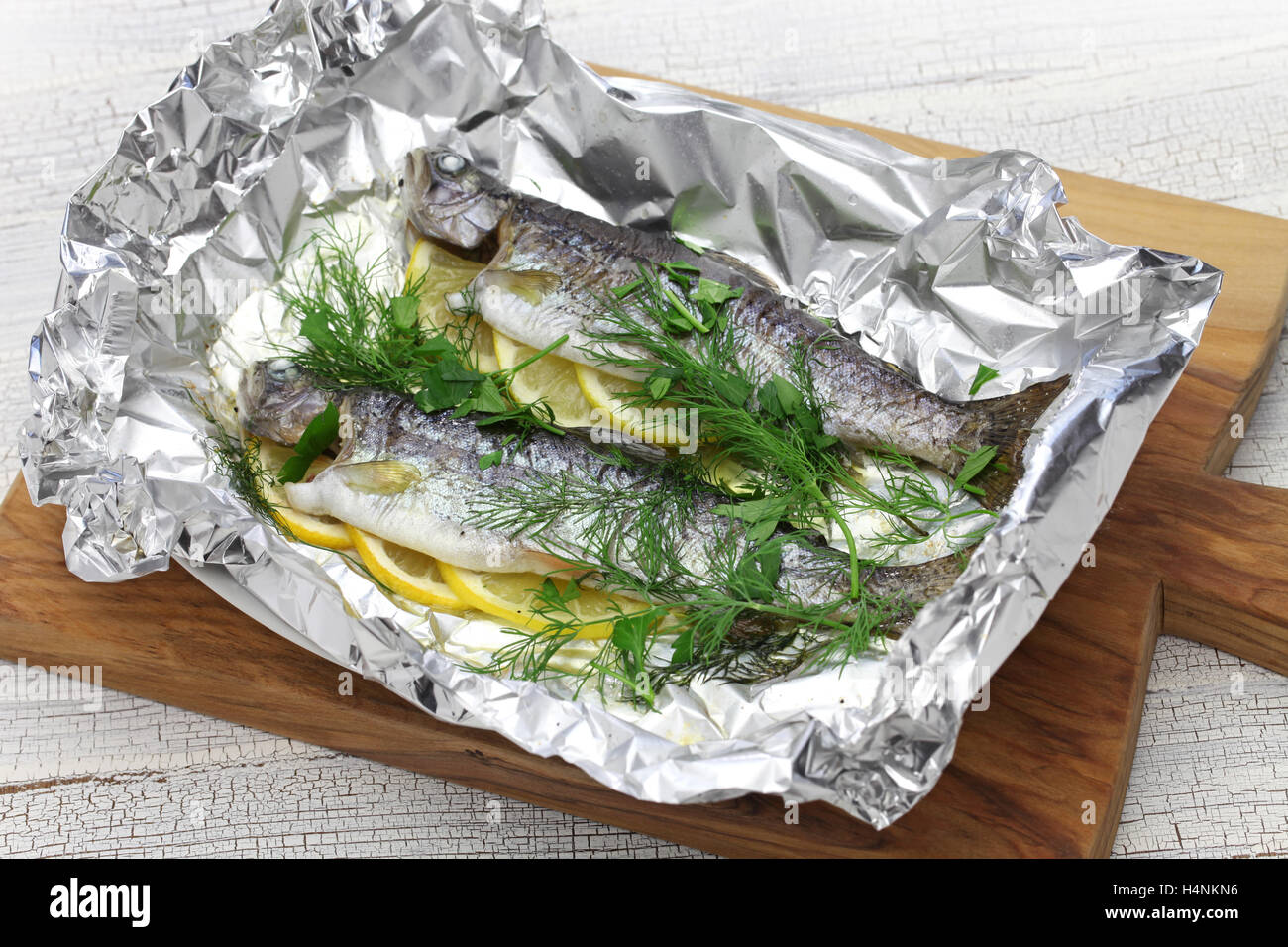 whole rainbow trout baked in foil on cutting board - Stock Image