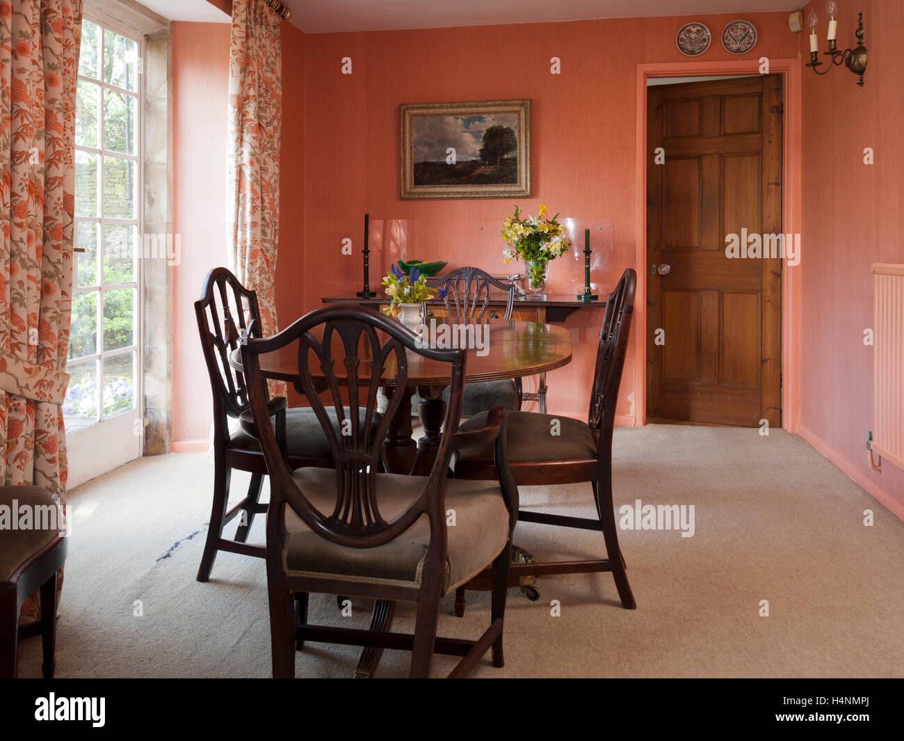 Traditionally furnished dining room with antique furniture and metal framed windows and french door - Stock Image