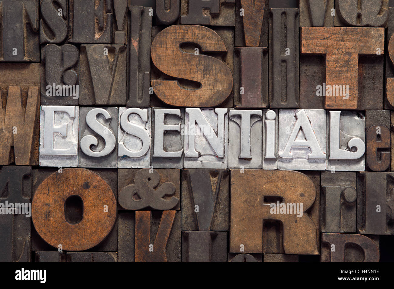 essential word concept made from metallic letterpress blocks inside many wooden letters background - Stock Image