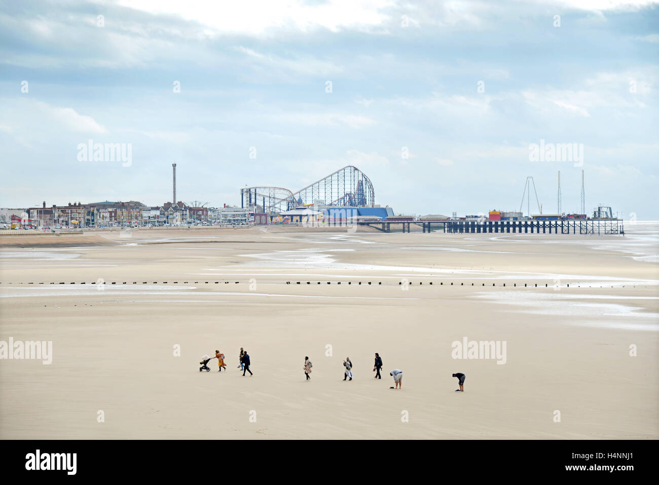 A family group walks across the beach between the Central Pier and The Pleasure Beach at Blackpool, England. - Stock Image