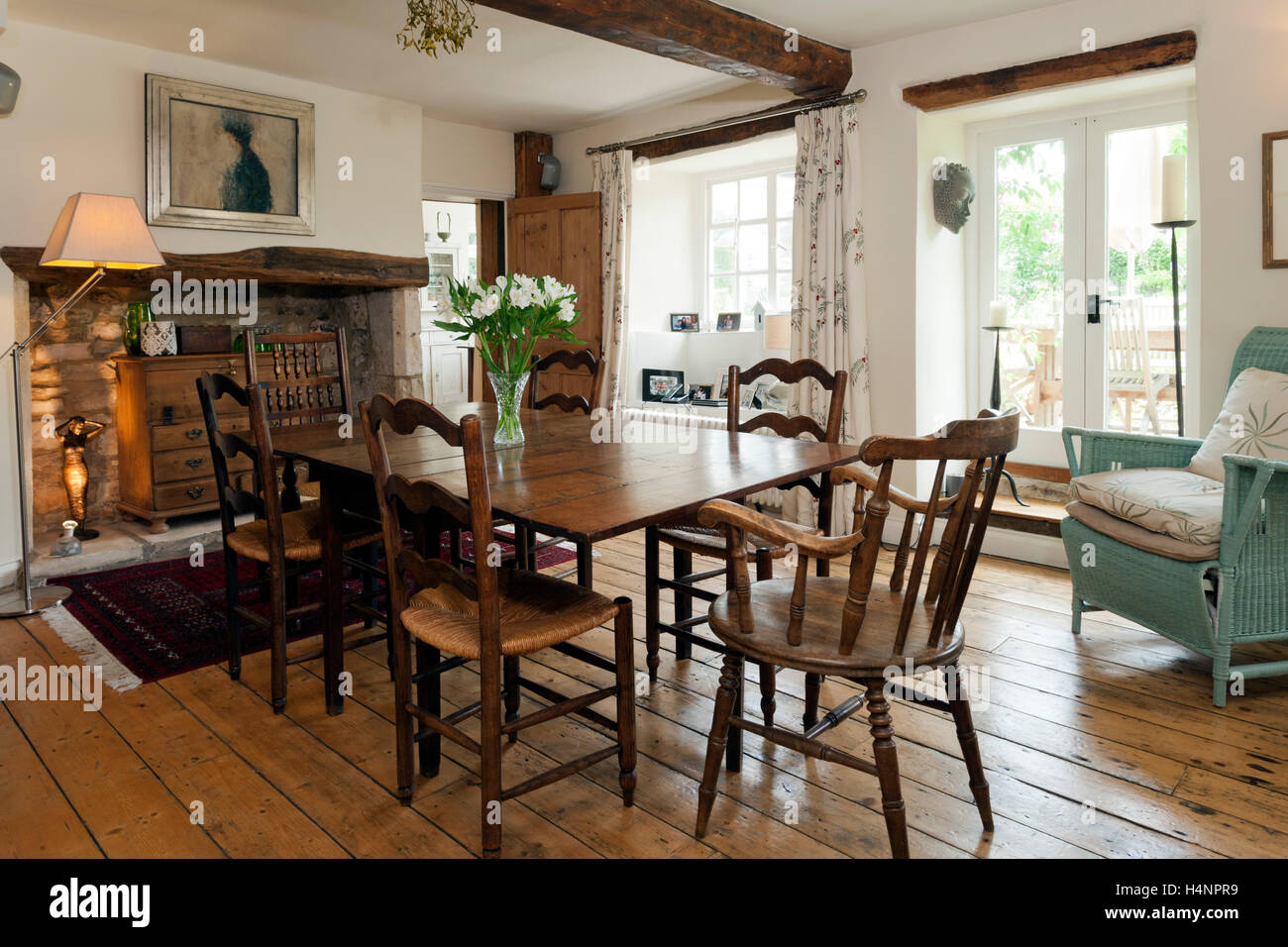 Antique furniture and stripped floorboards in a period cottage dining room - Stock Image