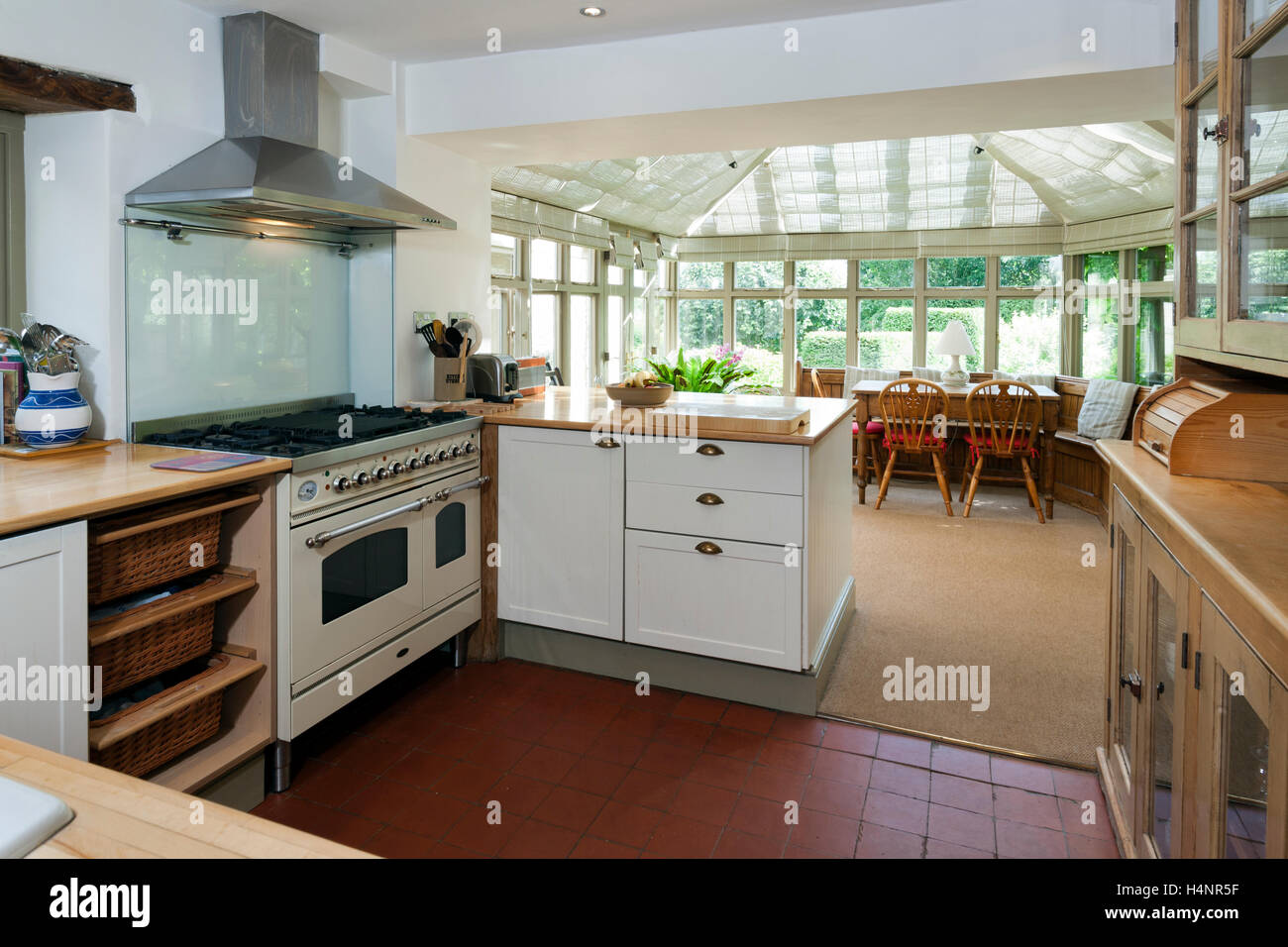 a small kitchen with a large conservatory dining room beyond stock image - Kitchen Conservatory