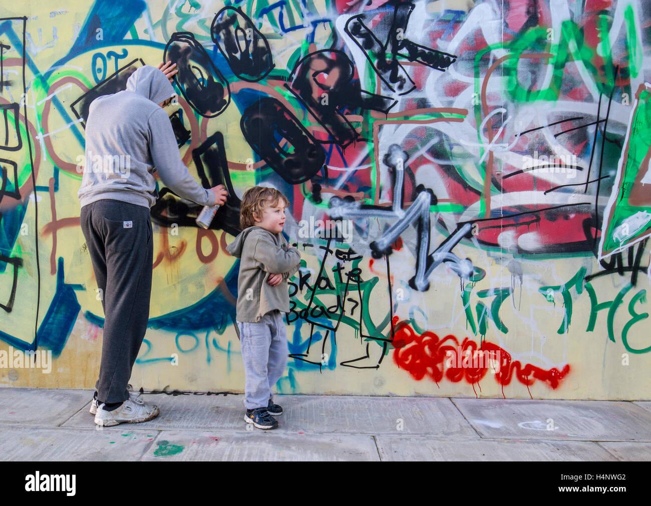 hoody teen spraying graffiti on wall with boy - Stock Image