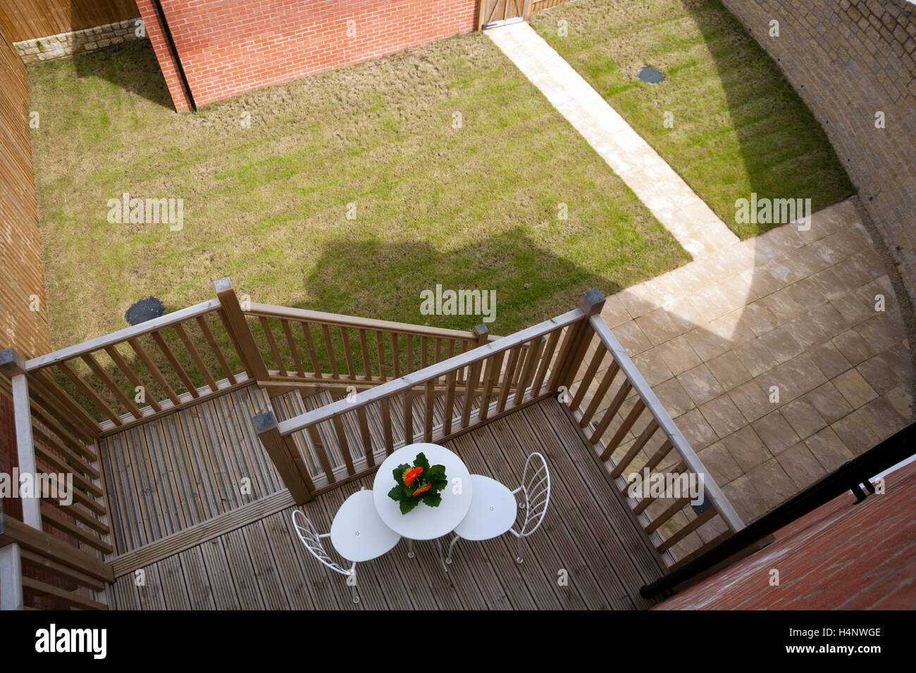 Looking down on a property development garden and decked balcony seating area - Stock Image