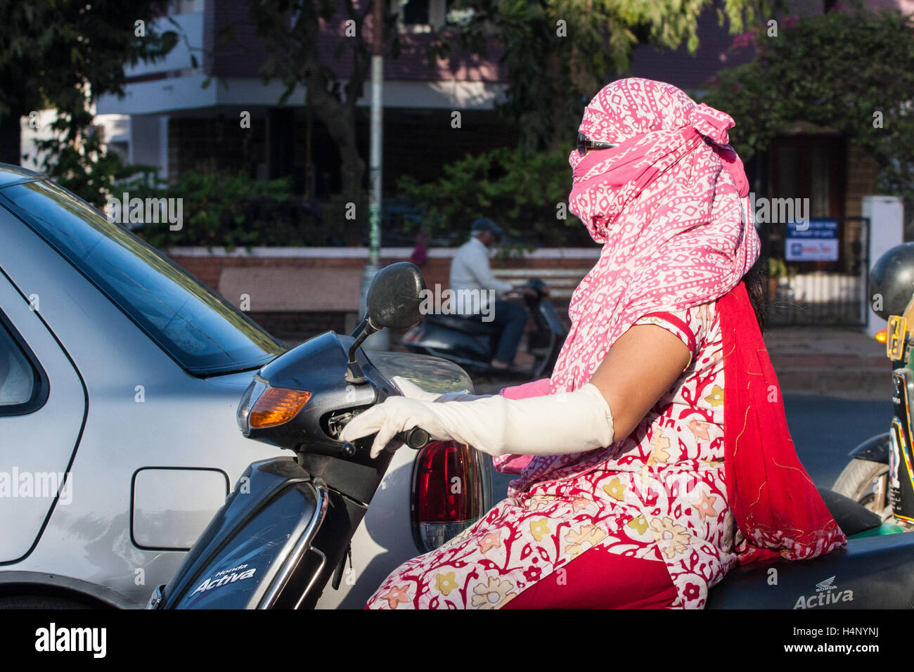 Face and arm covered woman, to protect from sun and pollution, riding driving on a scooter in centre of Ahmedabad,Gujurat. - Stock Image