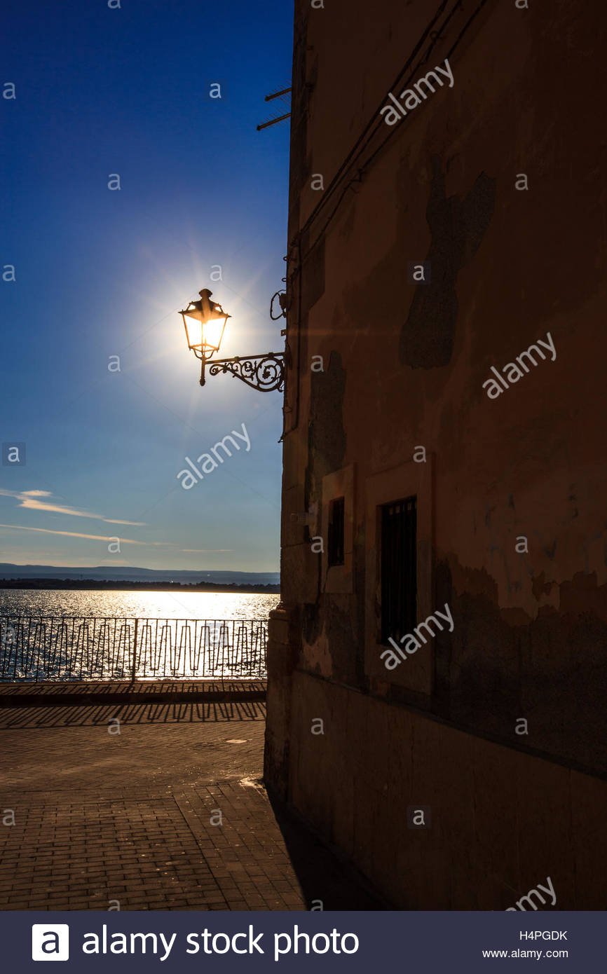 Sunlight shines through an old wrought iron lamp on a street corner on the island of Ortygia. - Stock Image