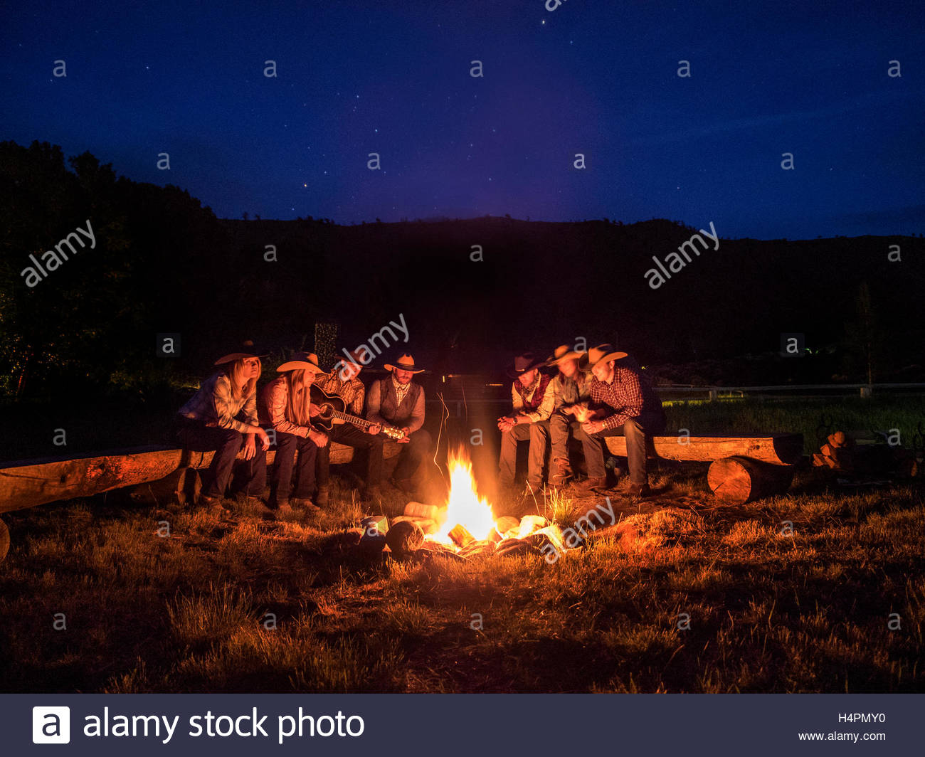 Wranglers at dusk around campfire on the CM Ranch. - Stock Image
