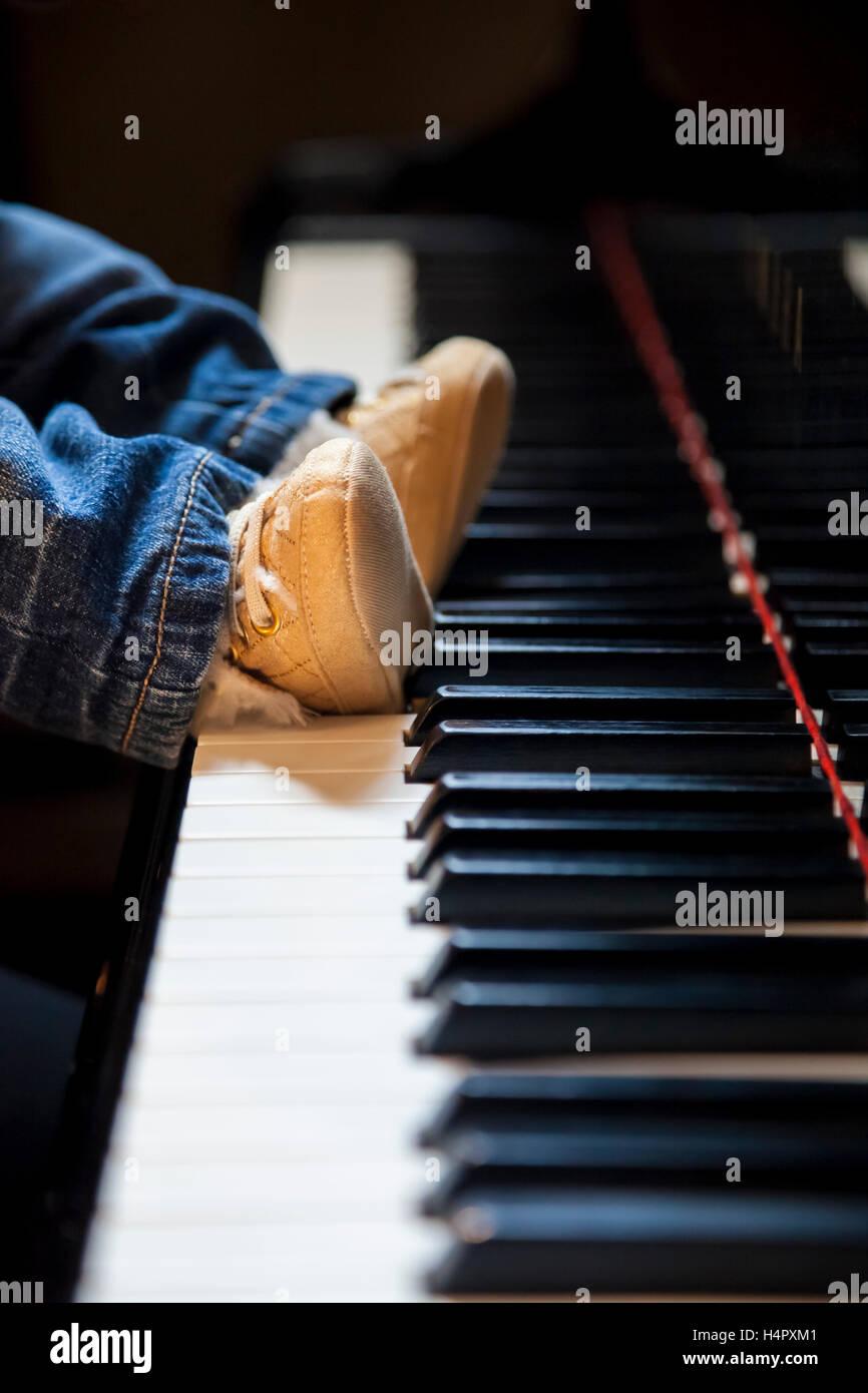newborn kid feet trying to play classic piano - Stock Image