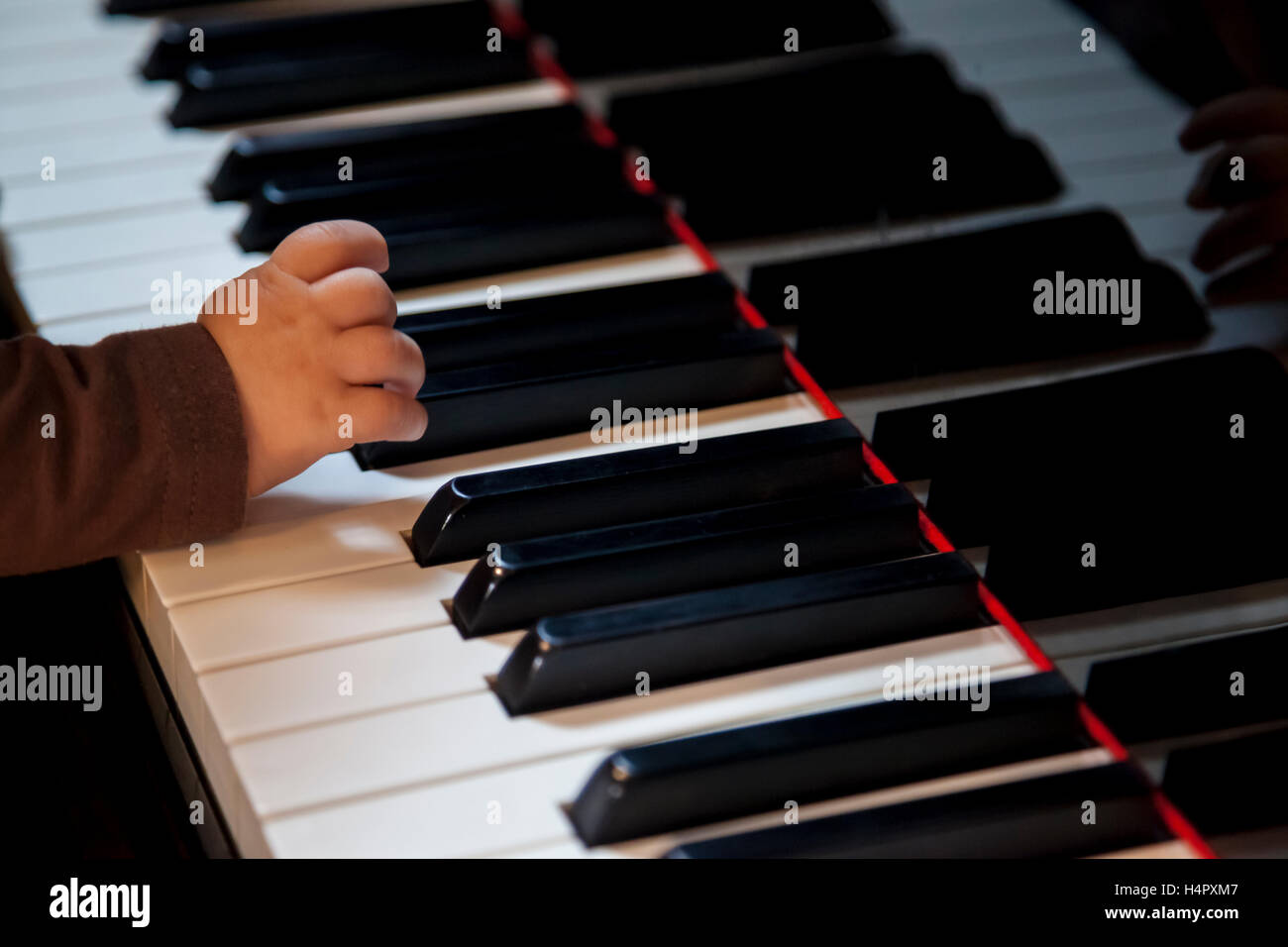 newborn kid hand trying to play classic piano - Stock Image