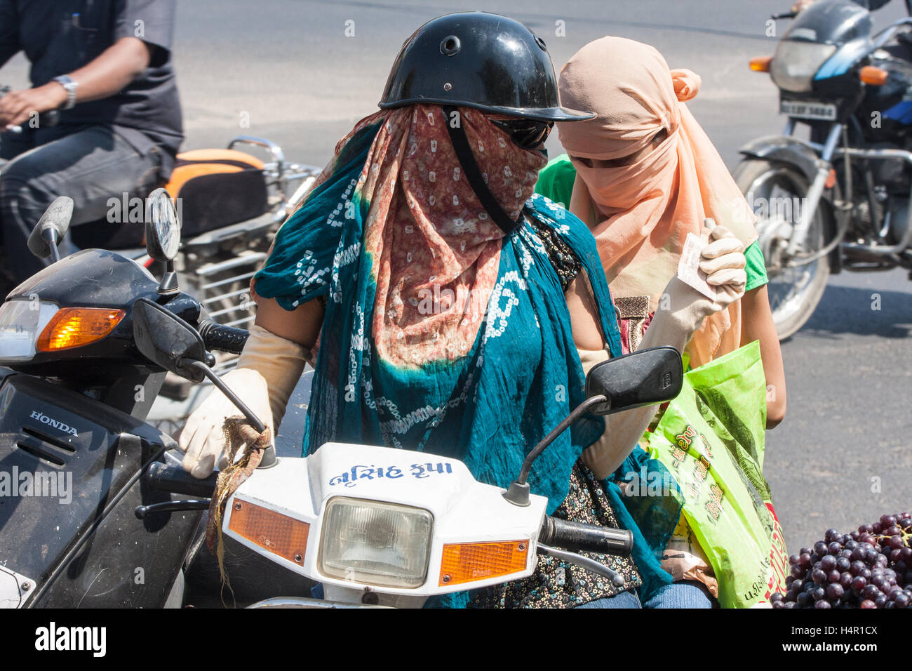 Face and arm covered women, to protect from sun and pollution, riding driving on a scooter in centre of Ahmedabad,Gujurat. - Stock Image