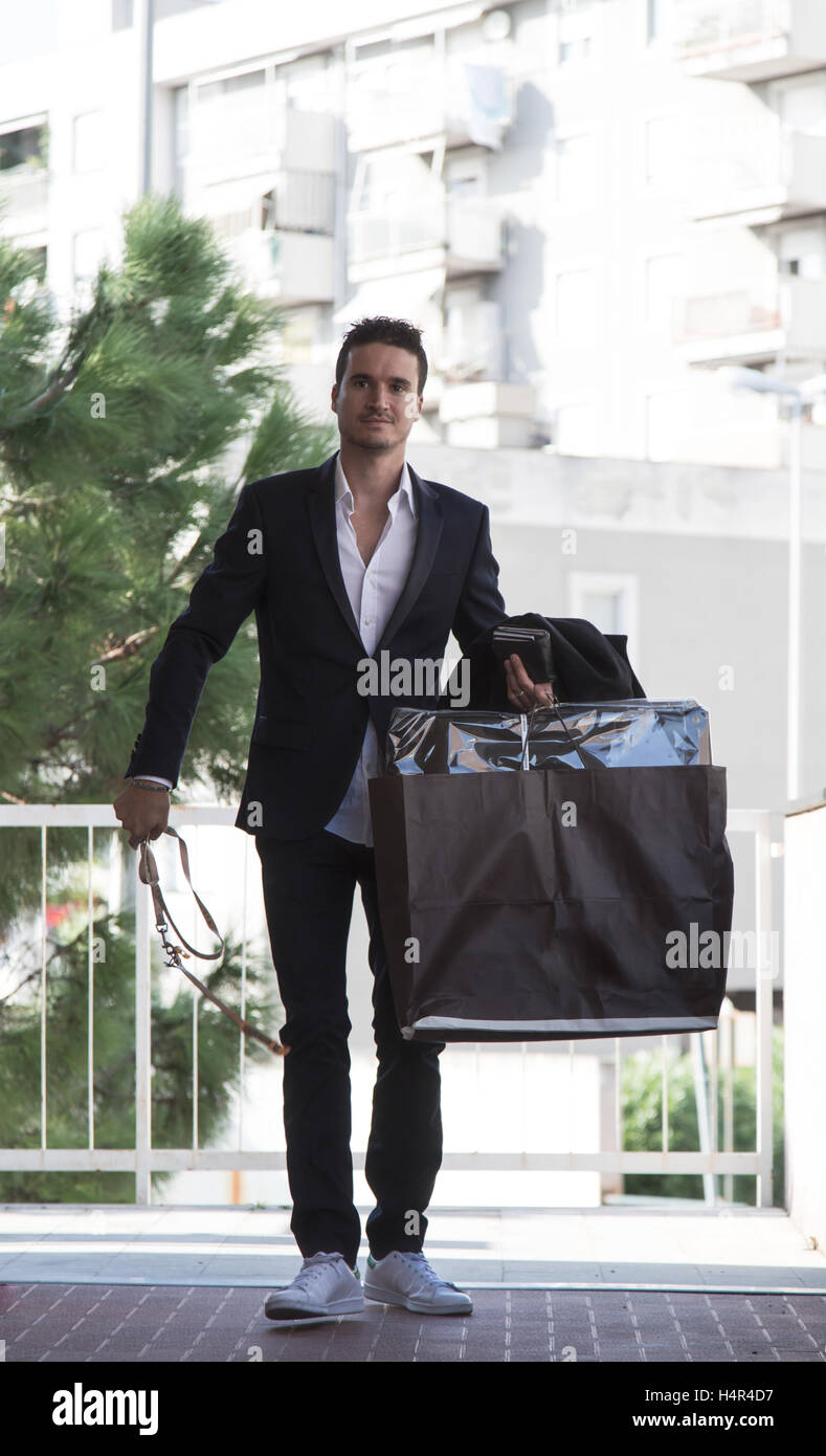 Handsome man in suit walking along sidewalk in urban setting with multiple large shopping bags - Stock Image