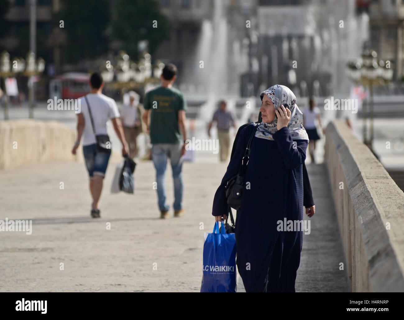 Muslim women walking  across the Stone Bridge, talking on the phone. Skopje, Macedonia - Stock Image