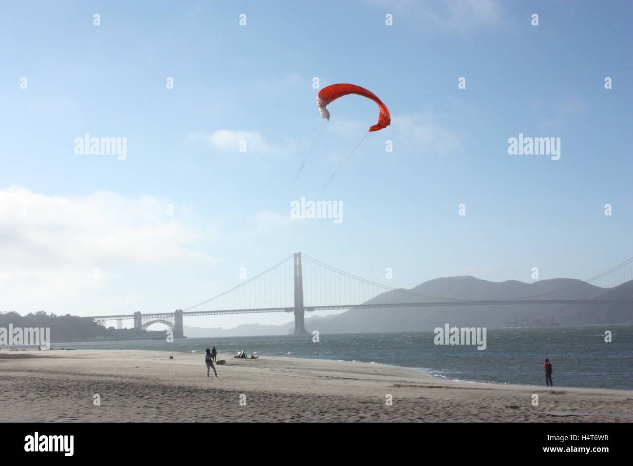 The Golden Gate Bridge with someone flying a kite on the beach next to the sea - Stock Image