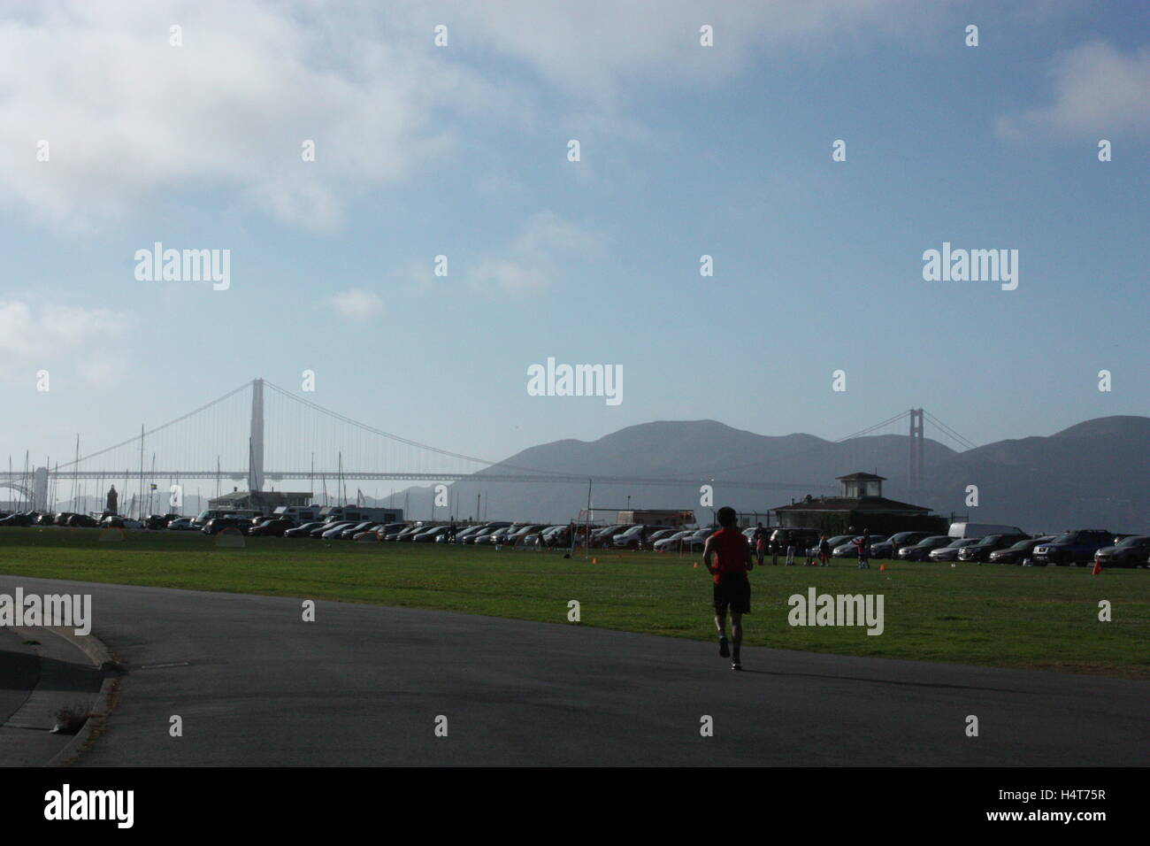Man cycling heading for the Golden Gate Bridge in San Francisco alongside the car park and the grass - Stock Image