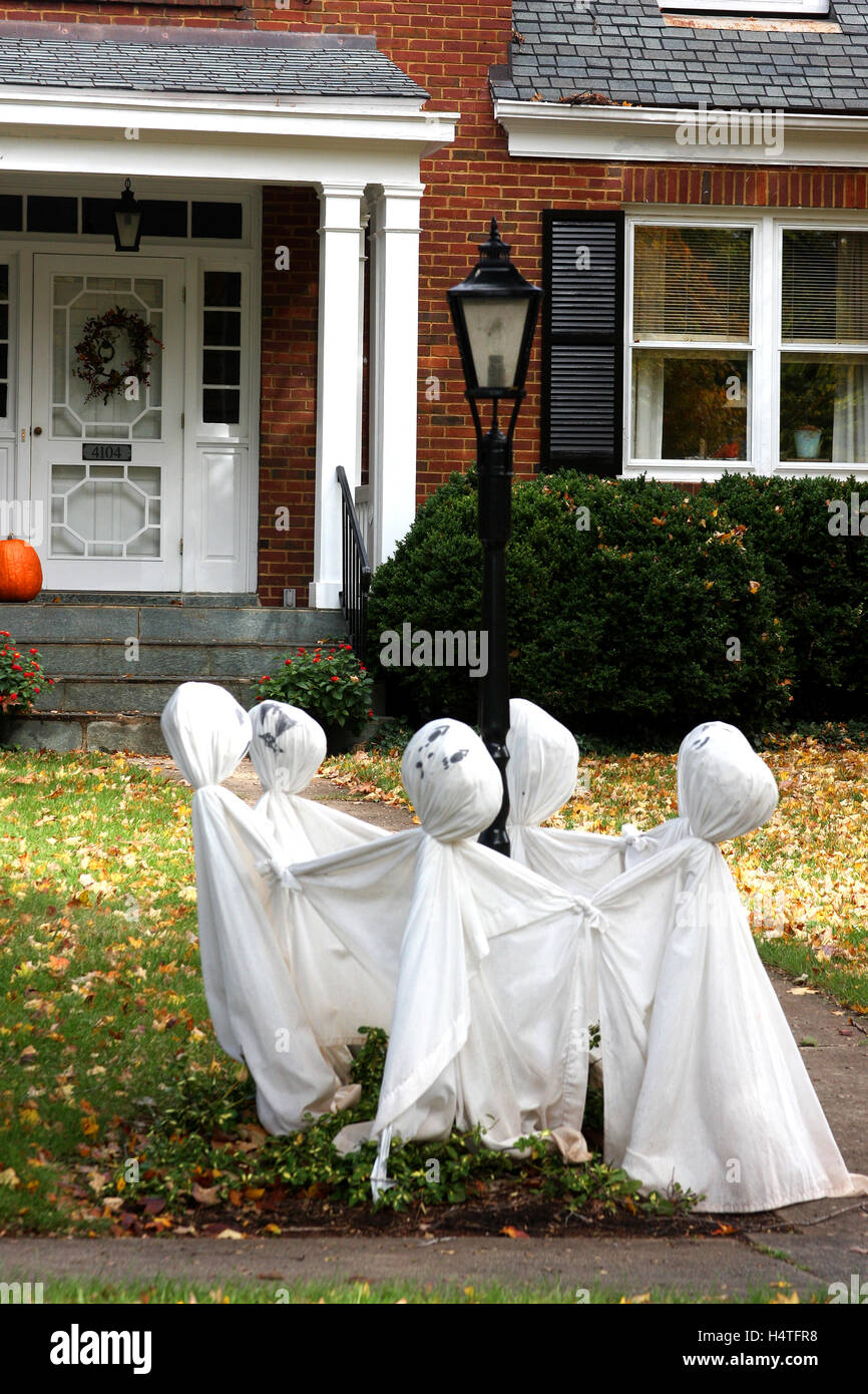 ghosts circling around a lamppost in the front yard - Stock Image