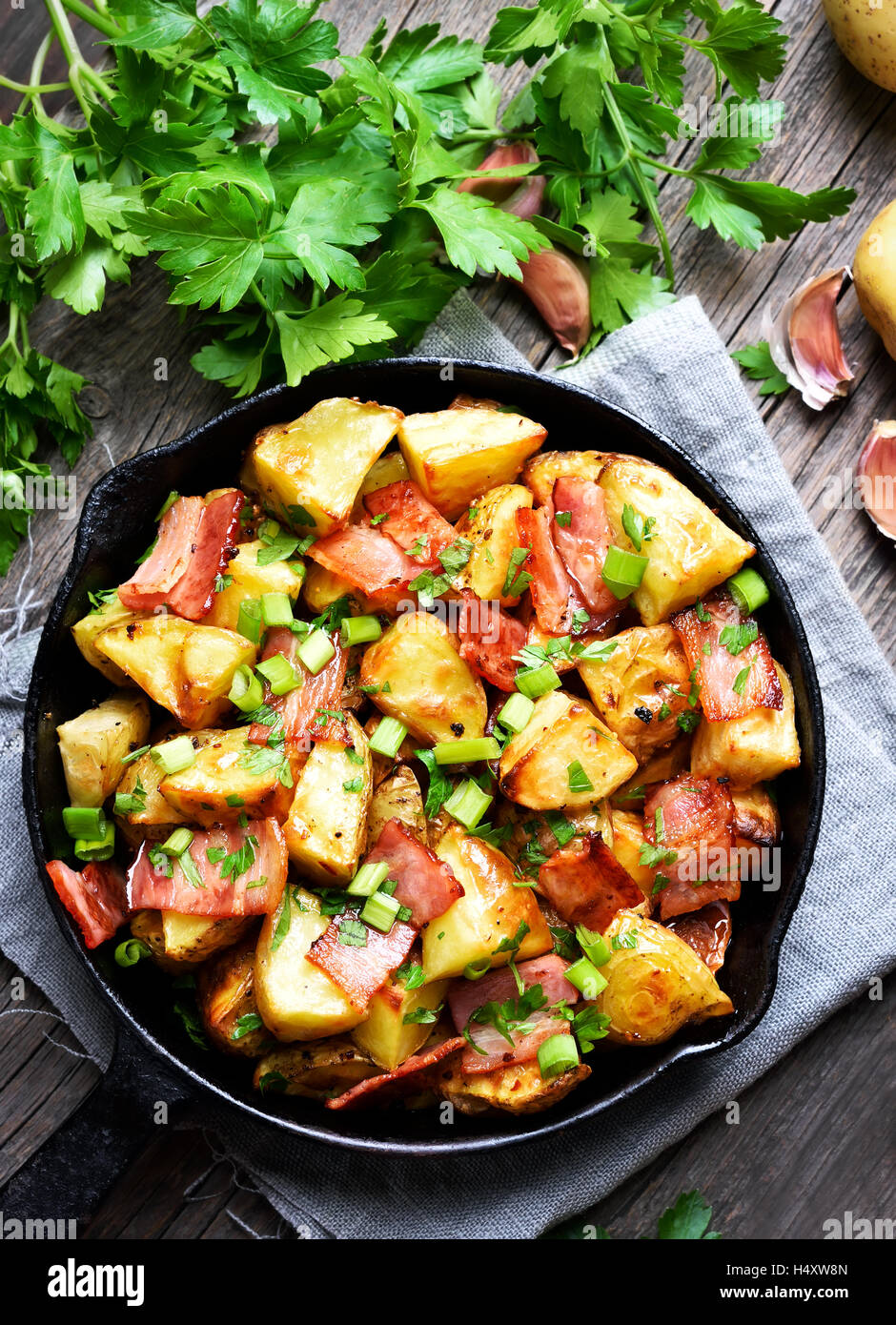Potatoes baked with bacon and onion, top view - Stock Image