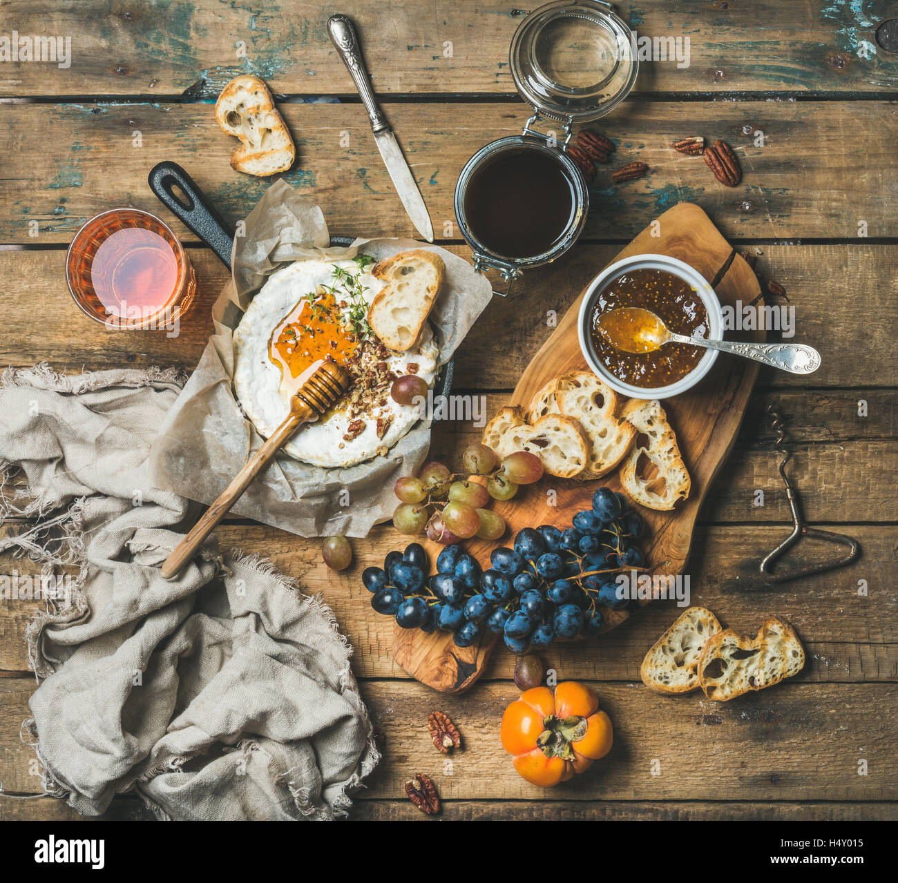 Cheese, fruit and wine set over rustic wooden background - Stock Image