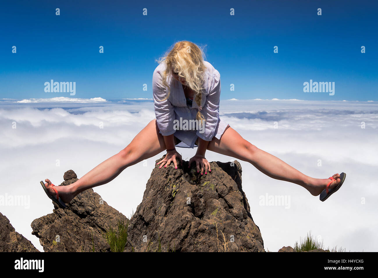 Young blonde woman acrobat making splits on rock on mountain's summit. - Stock Image