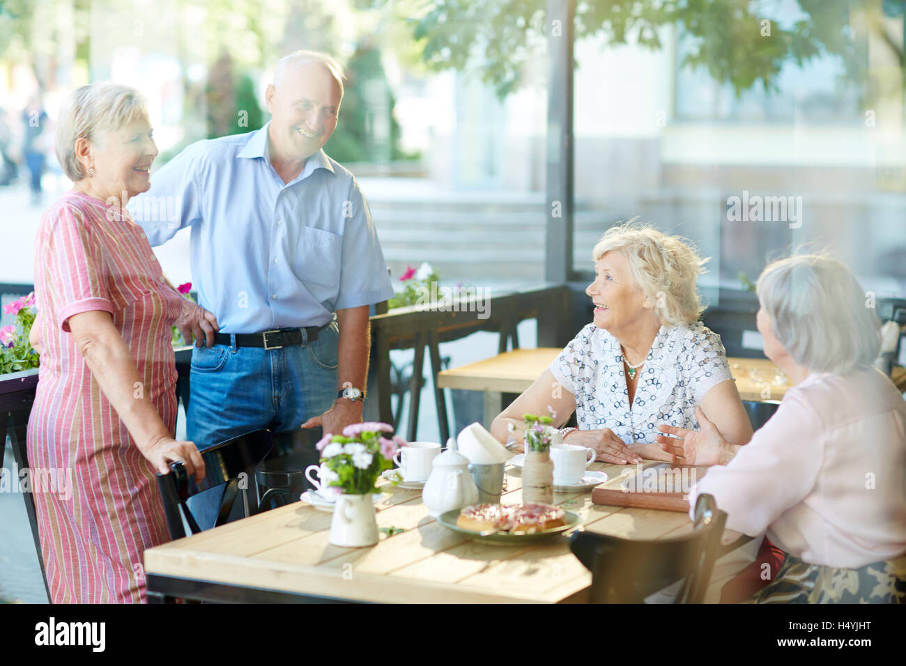 Carefree seniors having nice time in cafe - Stock Image