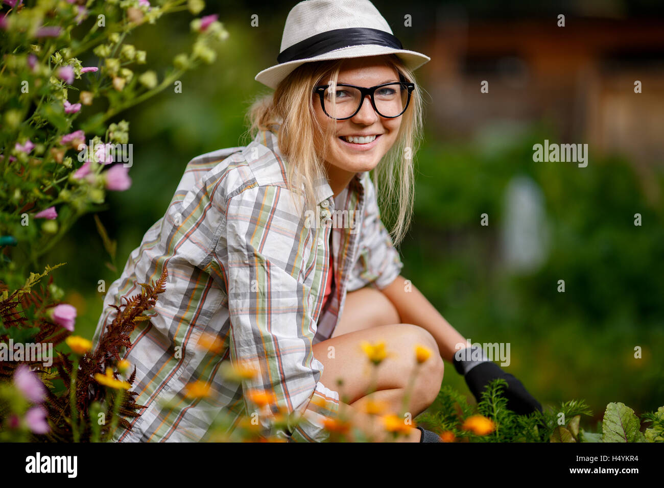 Portrait of happy young lady working in summer blossoming garden - Stock Image