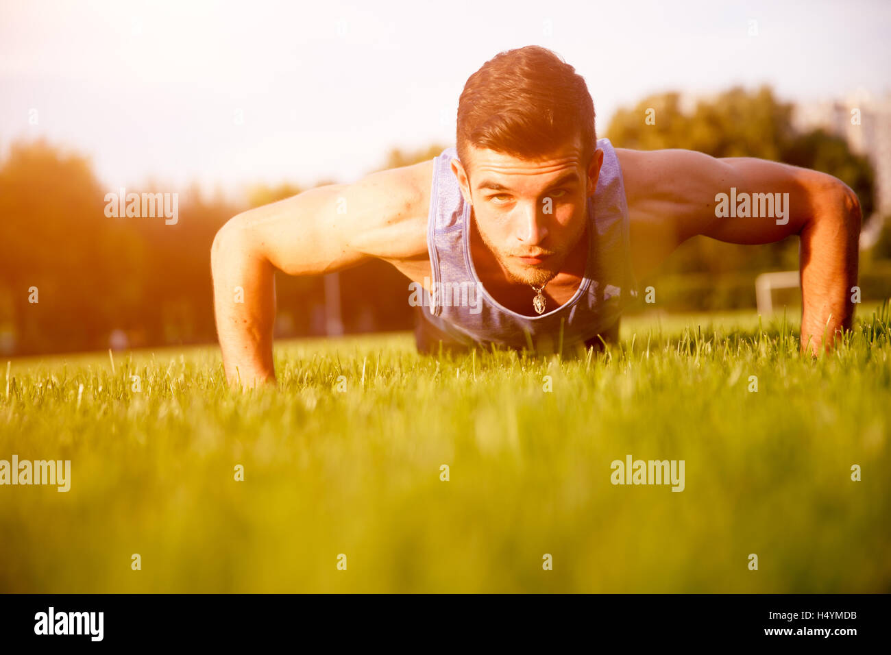 Young athletic guy in blue shirt press ups outdoors - Stock Image
