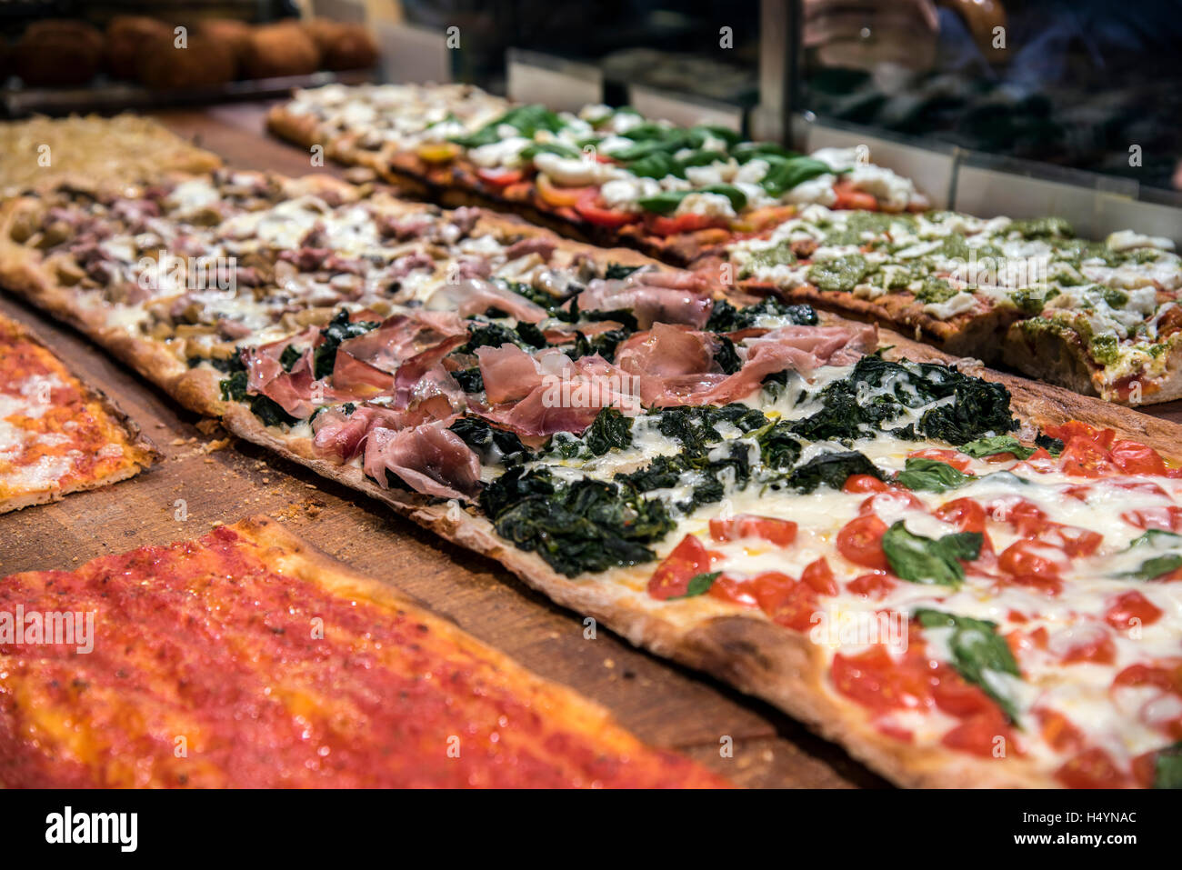 Different varieties of pizza served in a bakery of Trastevere district, Rome, Lazio, Italy - Stock Image