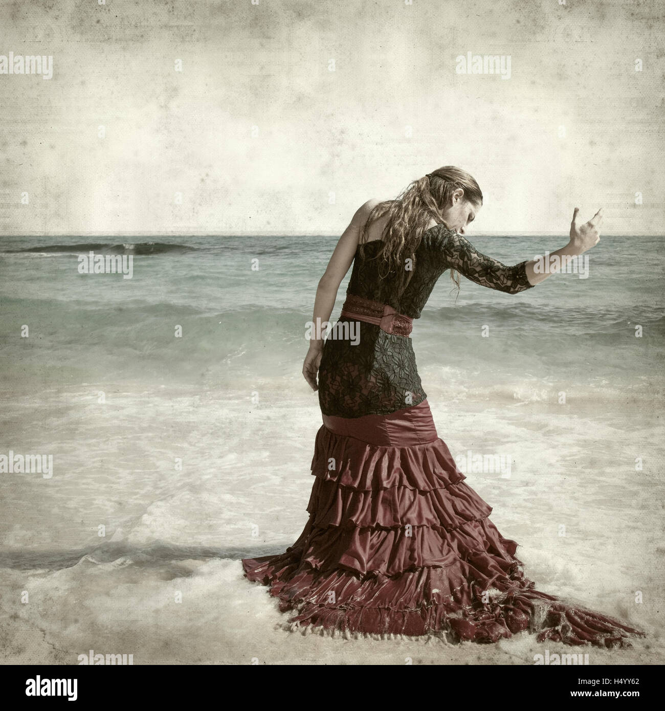 textured old paper background with flamenco dancer by the ocean shore - Stock Image