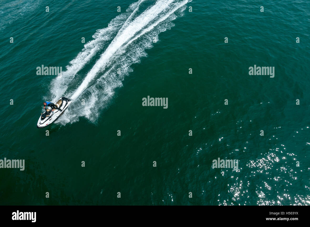 Man on a jet ski thunders over the water on the south coast of England - Stock Image