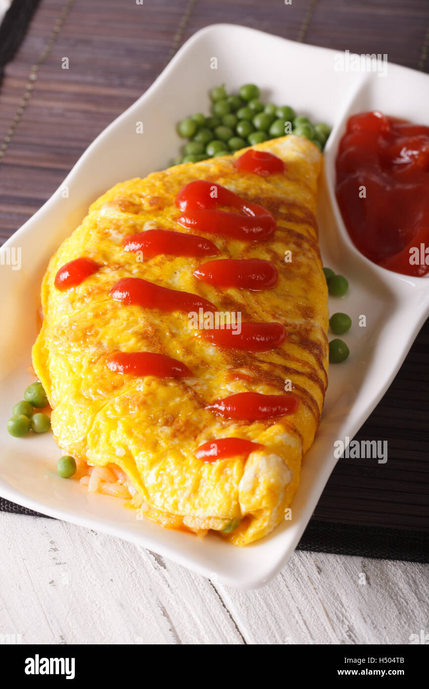 Japanese omelet stuffed with rice and chicken close-up on a plate. vertical - Stock Image