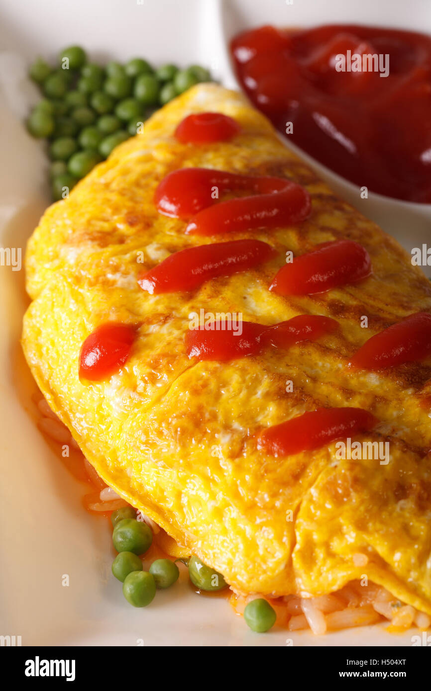 Omelet with rice, green peas and ketchup macro on a plate. vertical - Stock Image