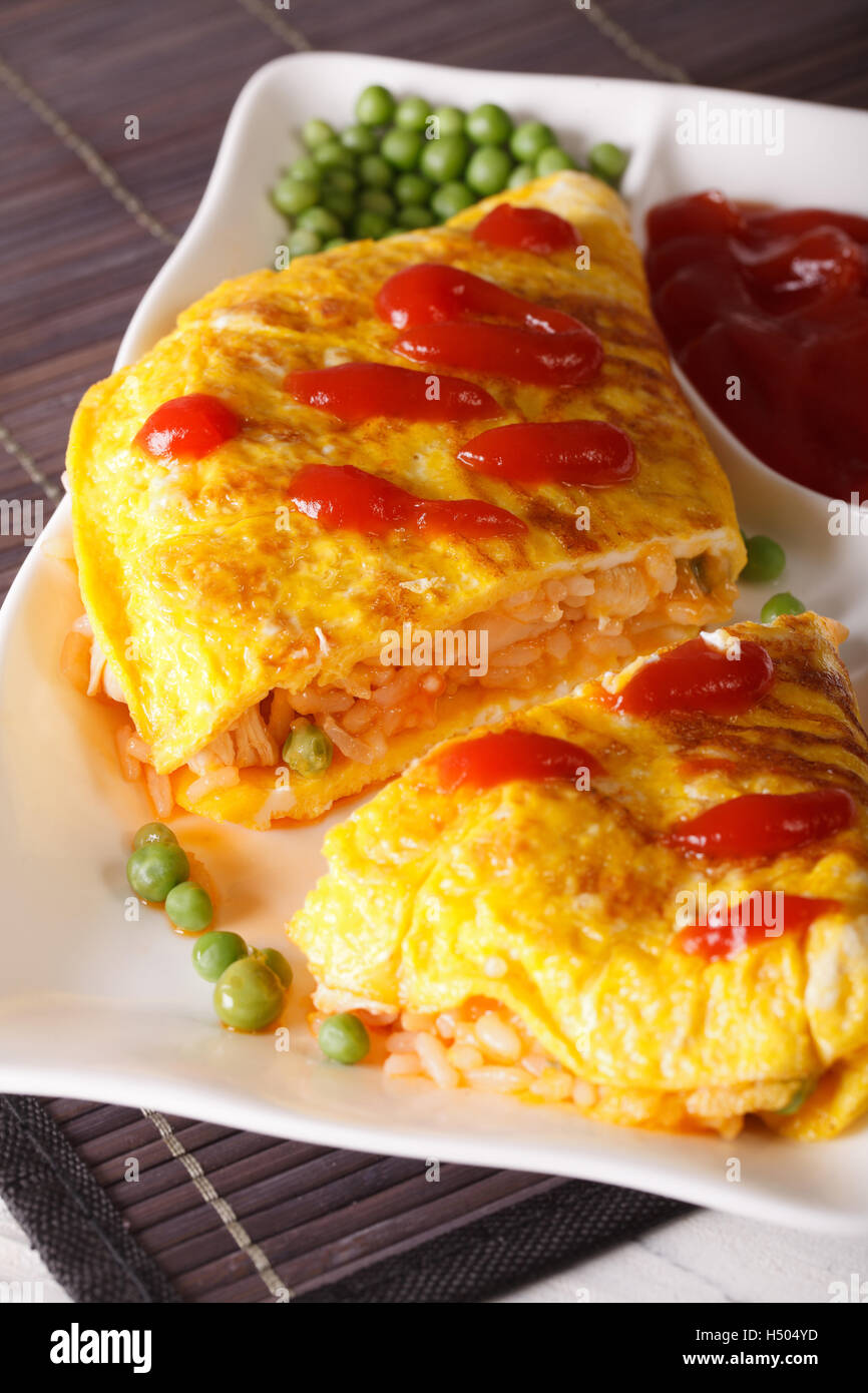 Japanese omelet with rice and ketchup Omurice close-up on a plate. Vertical - Stock Image