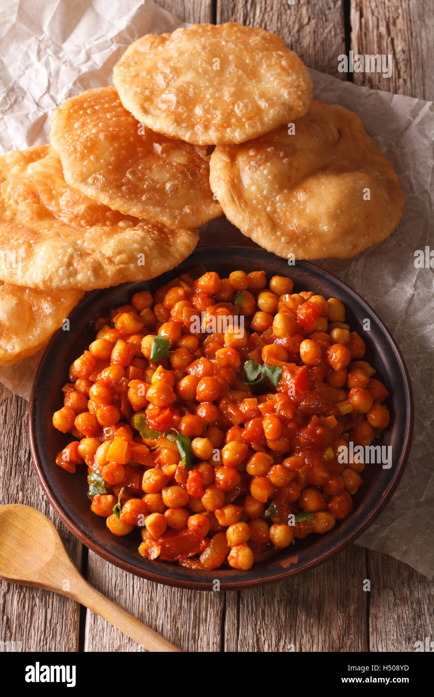 Indian Chana masala and puri bread close-up on the table. Vertical - Stock Image