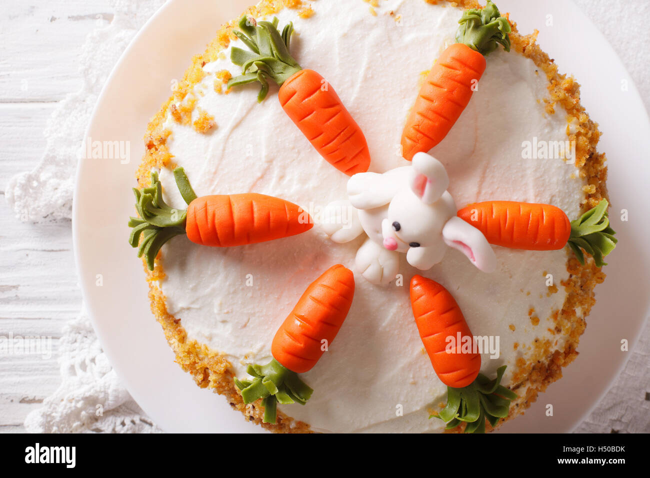 delicious carrot cake with candy bunny close-up on the table. horizontal top view - Stock Image