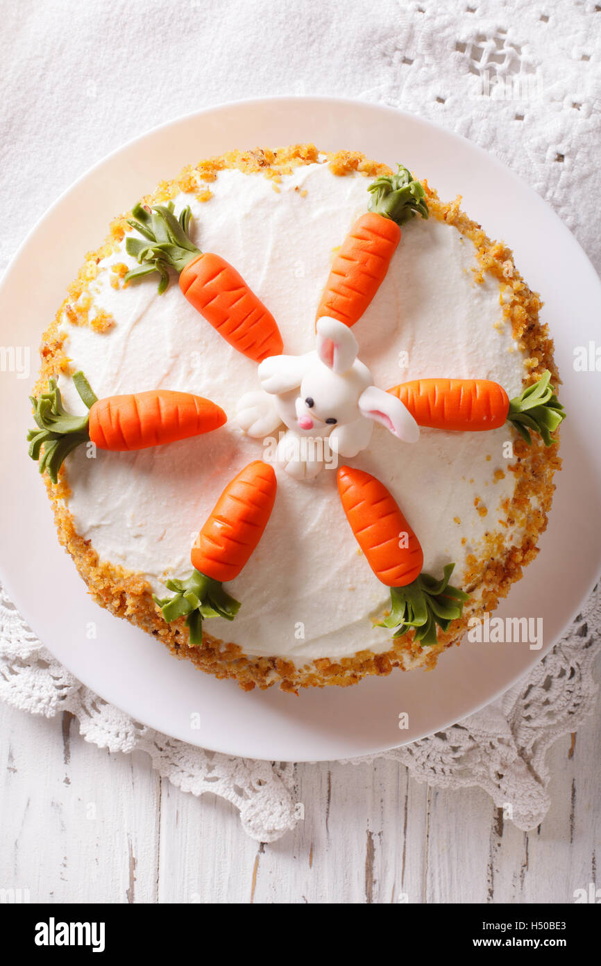 Beautiful carrot cake with candy bunny close-up on the table. vertical top view - Stock Image