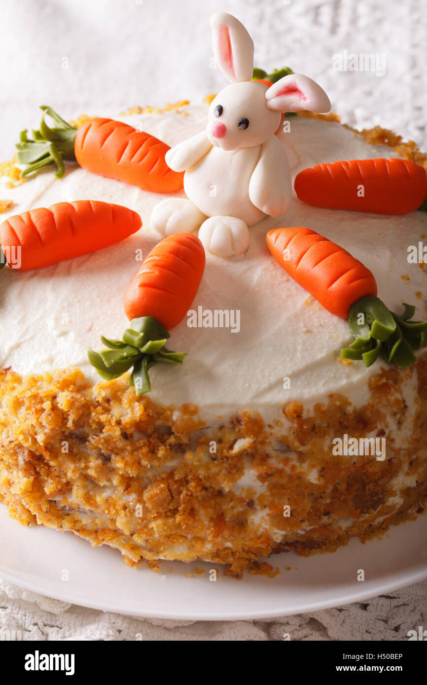carrot cake with candy bunny close-up on a plate on the table. Vertical - Stock Image
