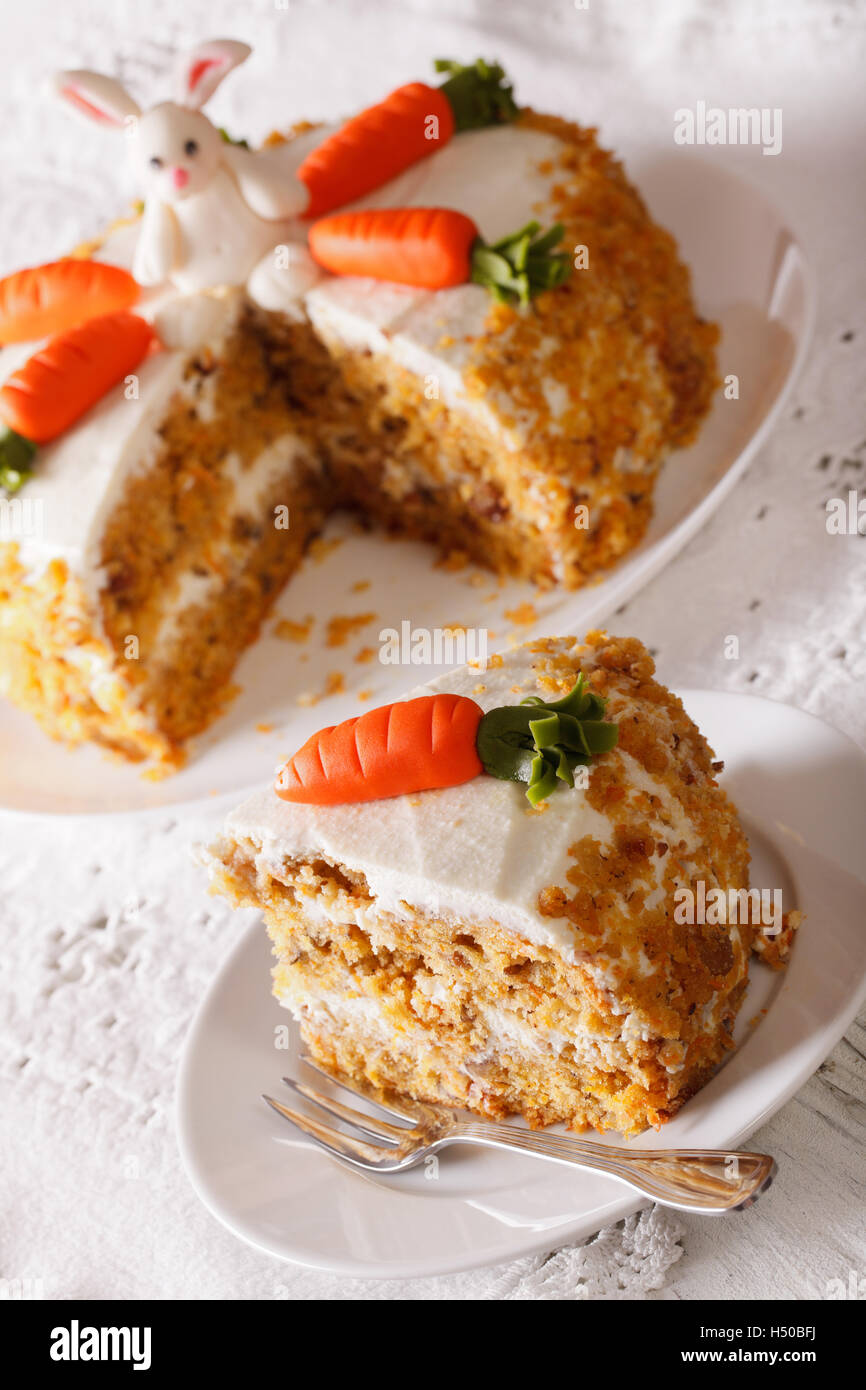 Beautiful carrot cake with decorations and slice close-up on the table. vertical Stock Photo