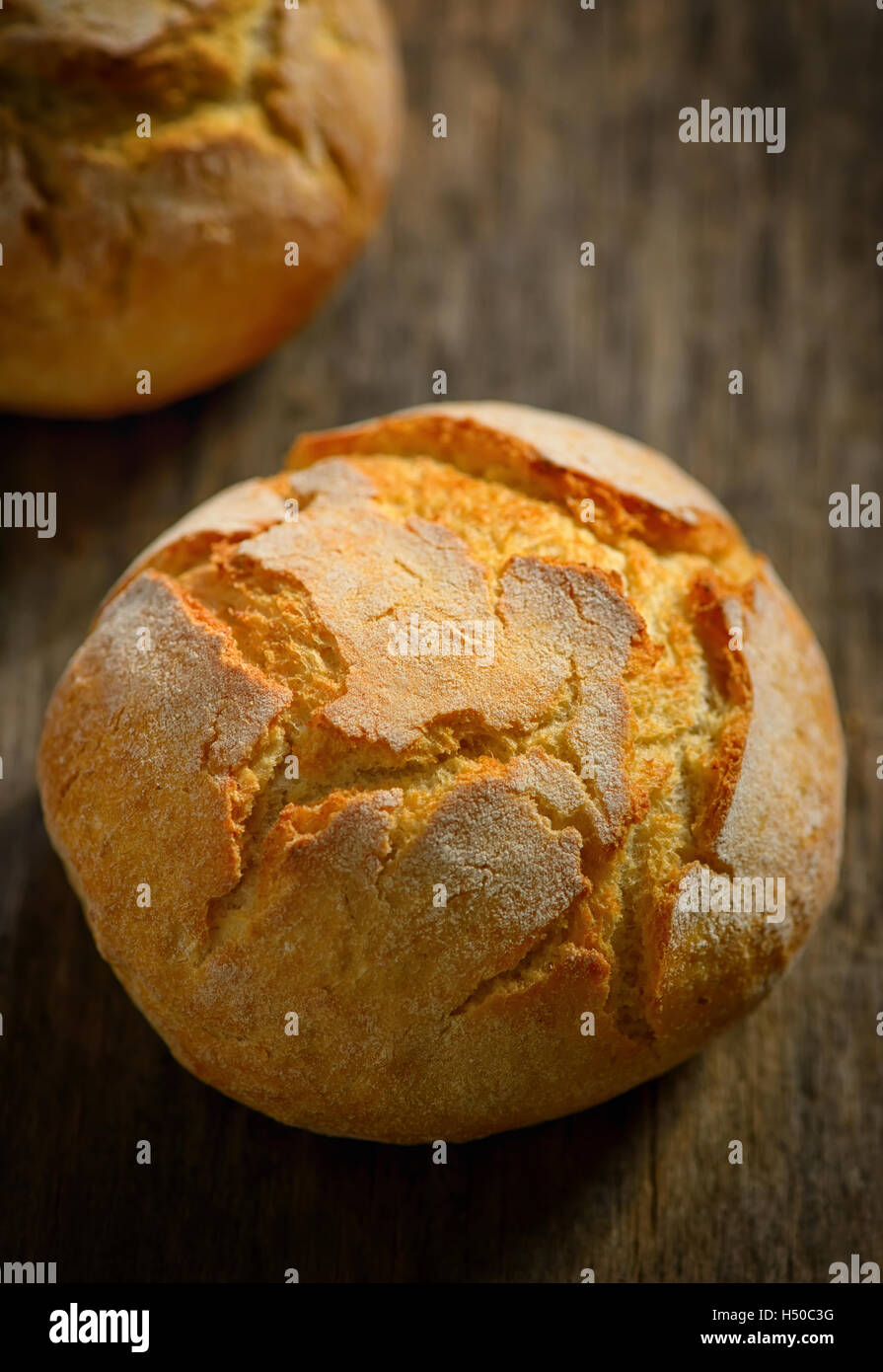 traditional homemade round bread on wooden table - Stock Image