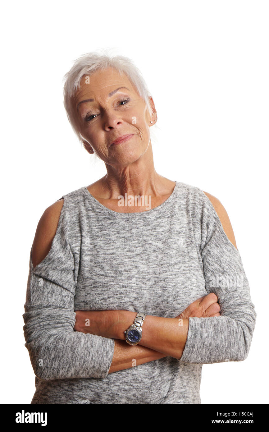 mature woman with arms folded and head tilted - Stock Image