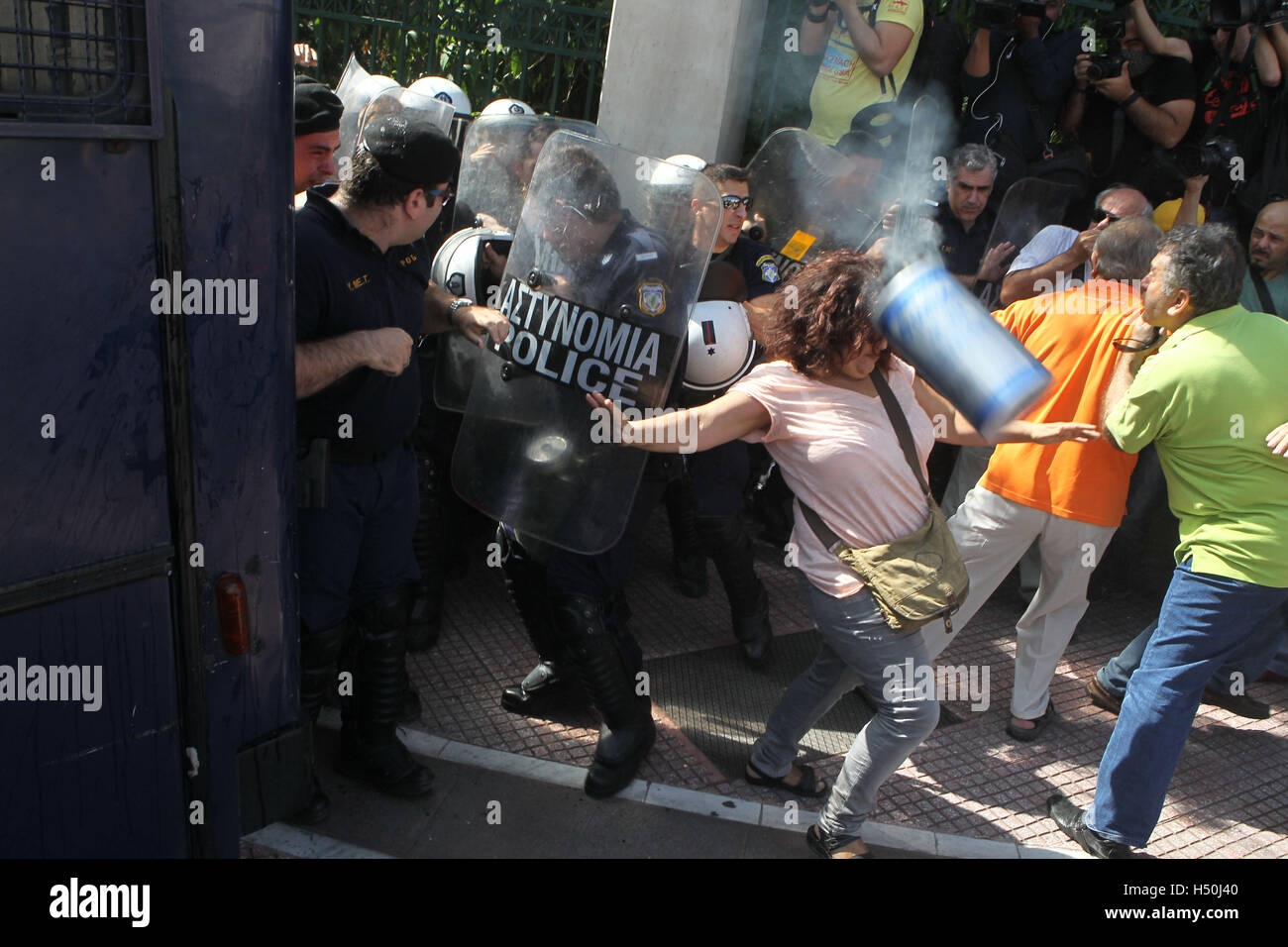 Elderly people clash with riot police during anti-austerity protest against pension cuts in central Athens near - Stock Image