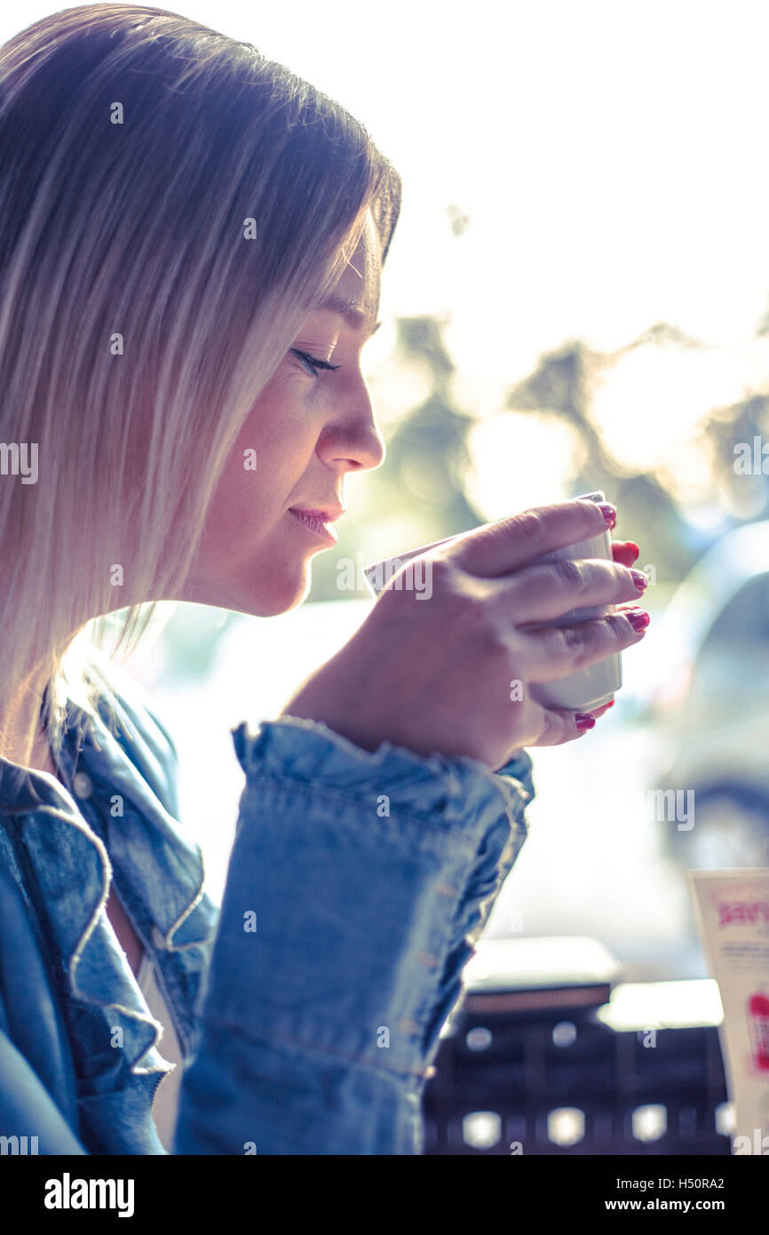 Portrait of young woman drinking coffee - Stock Image