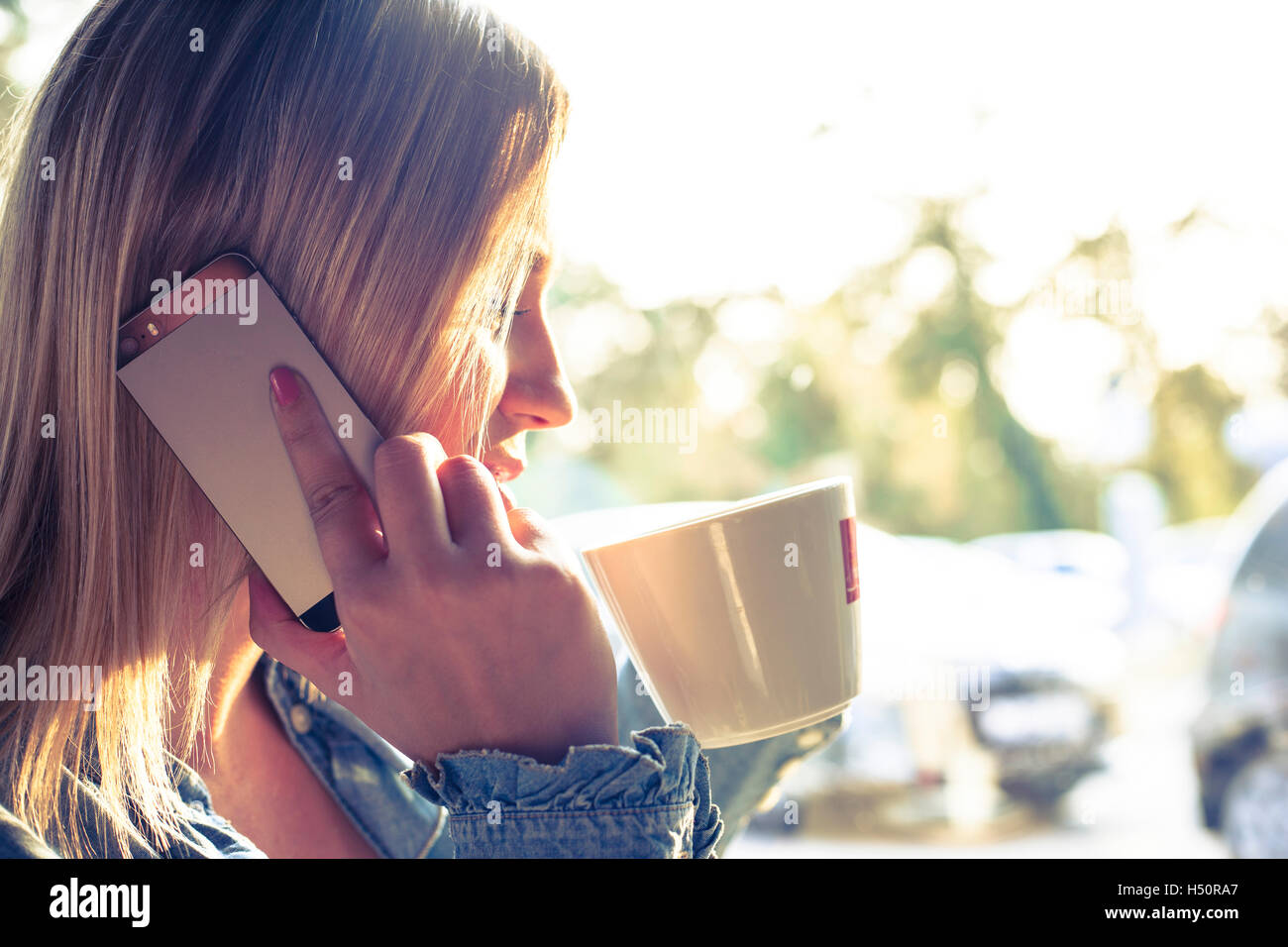 Young woman drinking coffee and talking on mobile phone - Stock Image