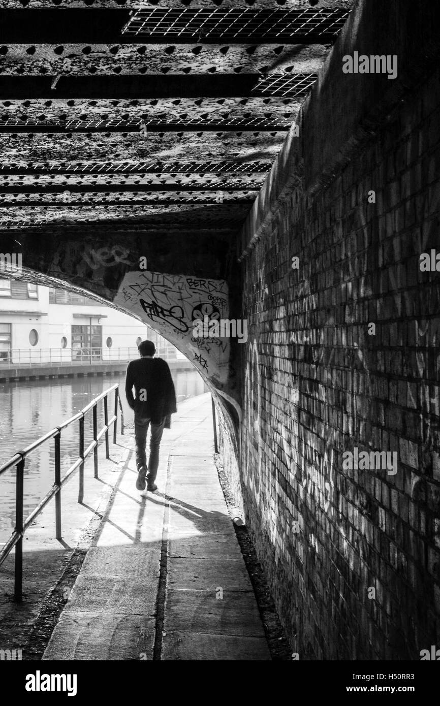 Black and white image of a single person walking underneath a bridge on the towpath of Regent's Canal, silhouetted - Stock Image