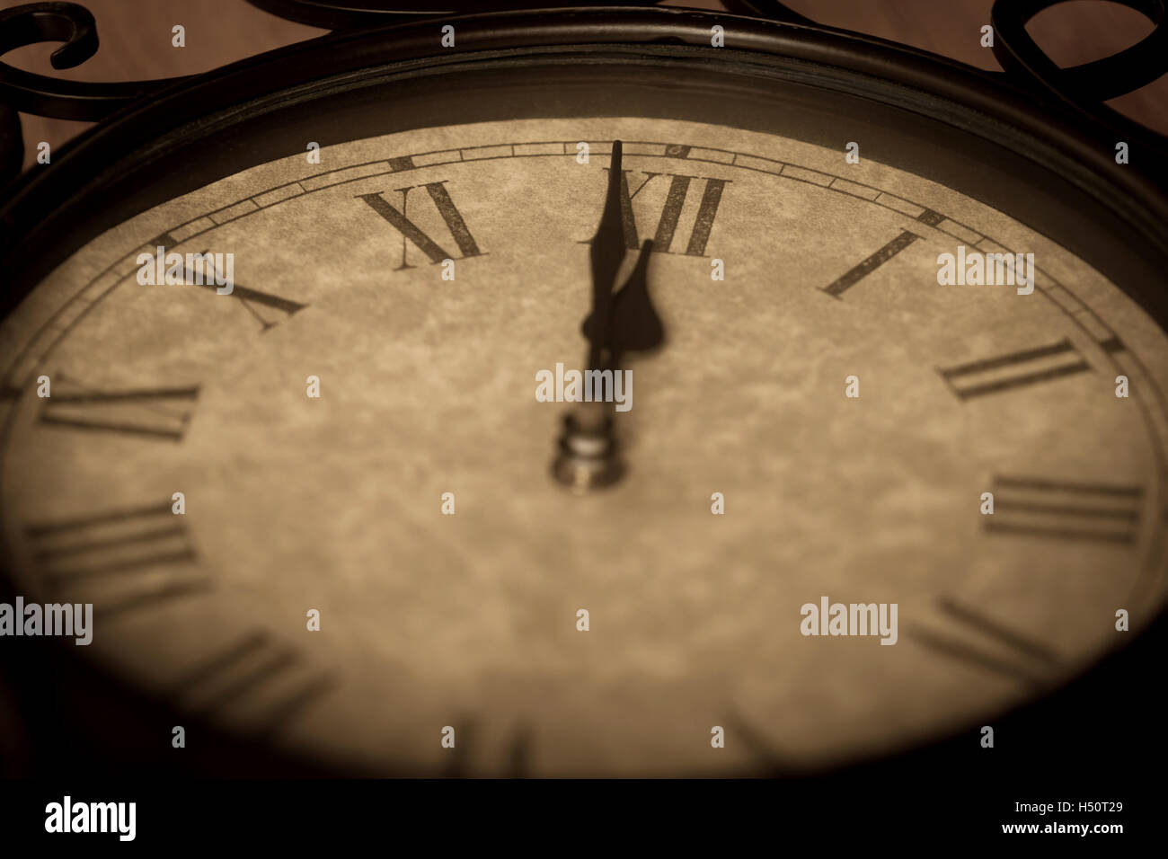 Antique clock showing minute to midnight with deliberate focus on the roman numeral 12 and shallow depth of field - Stock Image